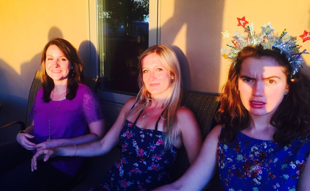 three girls siting in a row, one wearing a birthday crown