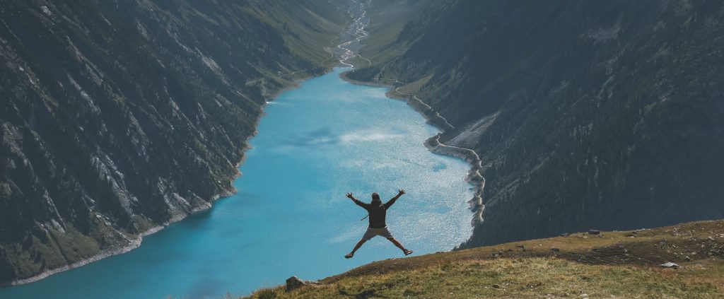 man jumping spread eagle over a big river ravine