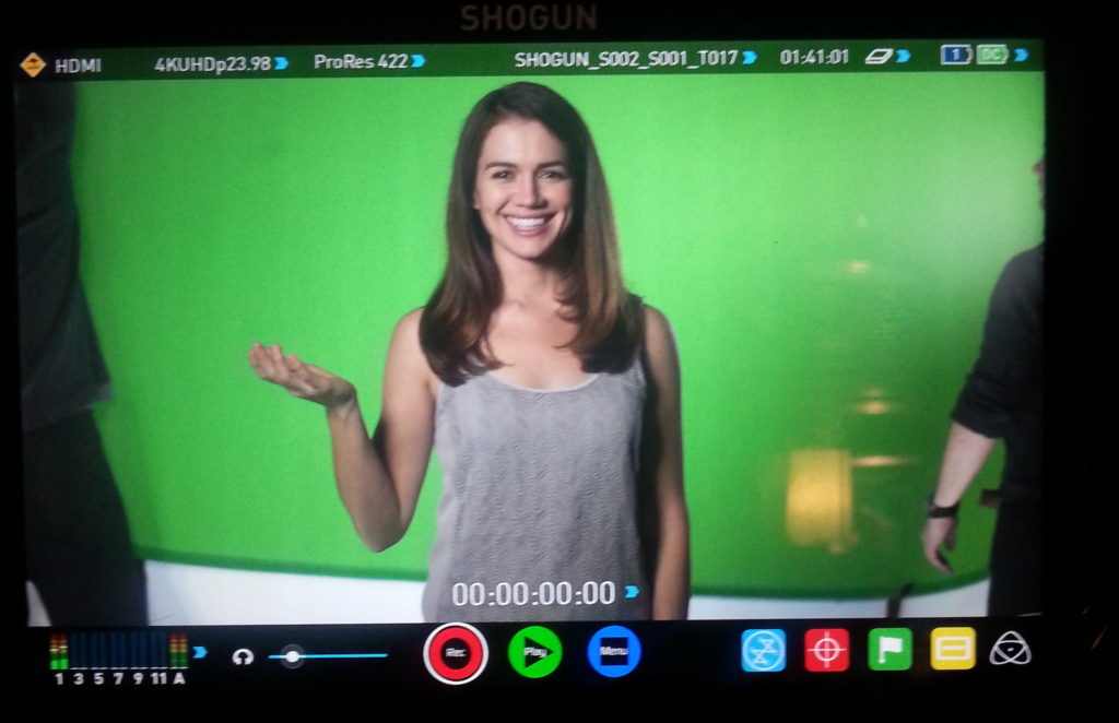 woman smiling infront of green screen