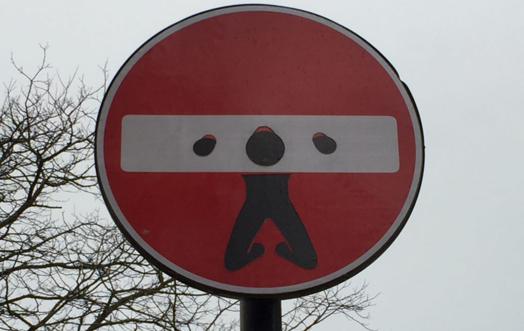 road sign with graffiti dran to put man in gallows