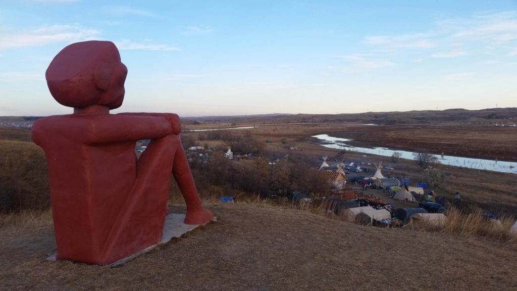 sculpture of pensive native american sitting atop a hill