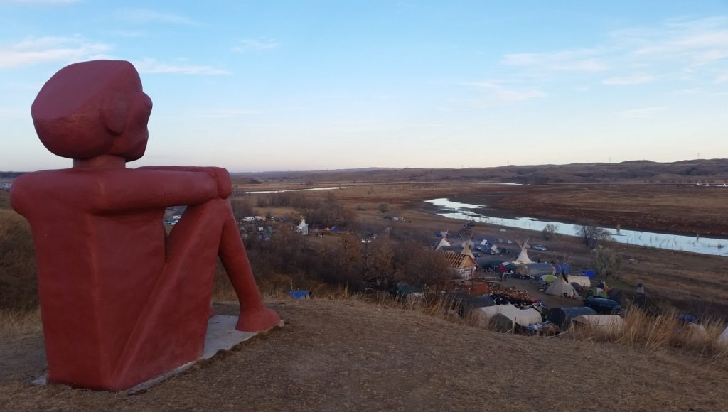 A sentry Native American sculpture overlooking the Land and Sacred Stone Camp at Standing Rock