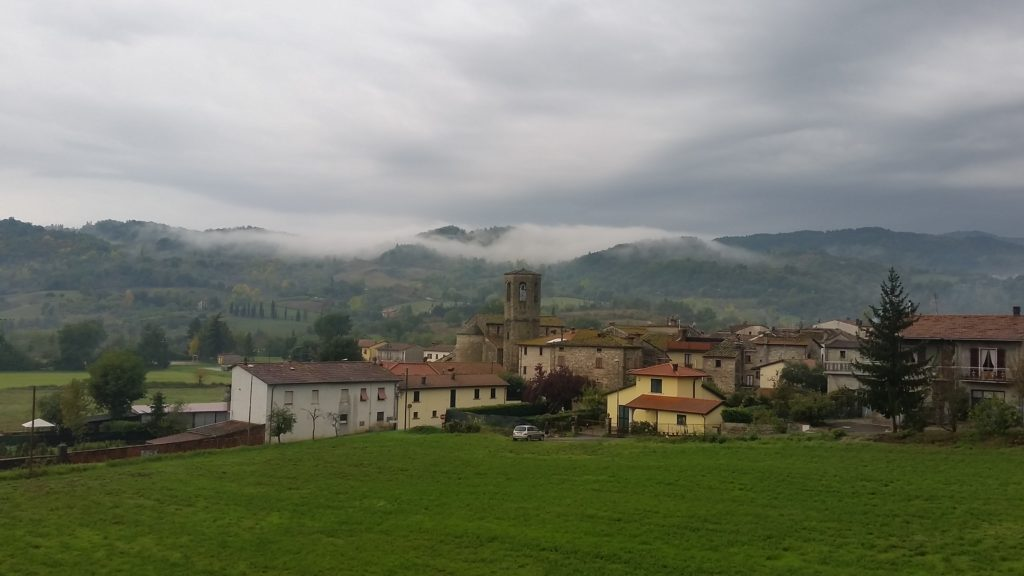 clouds rolling in on hills over village in tuscany
