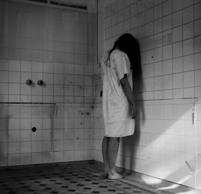 girl in insanity asylum with head against wall