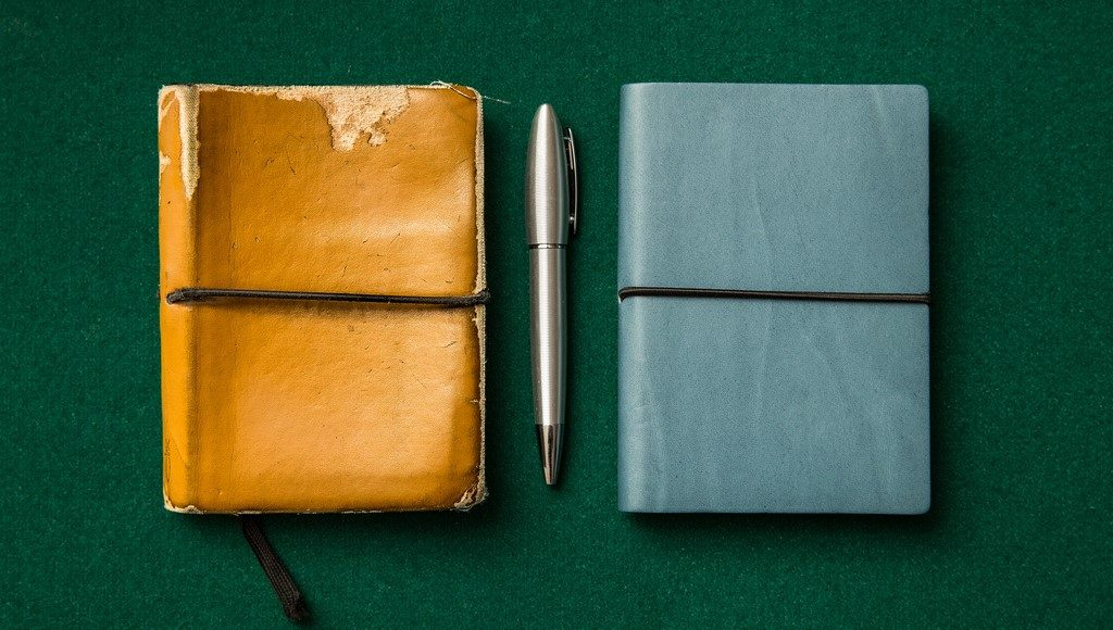 two journals and a pen between
