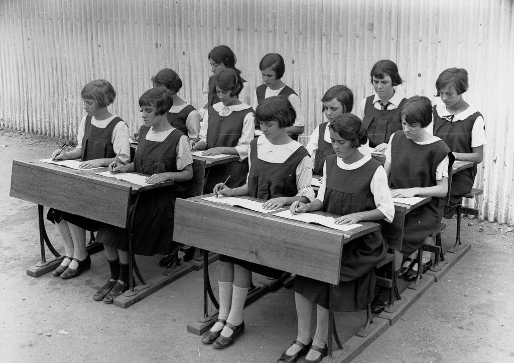 girls sitting at school desk in 30s