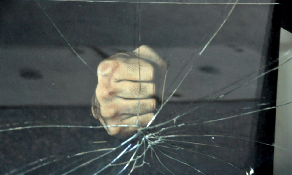 fist breaking a pane of glass