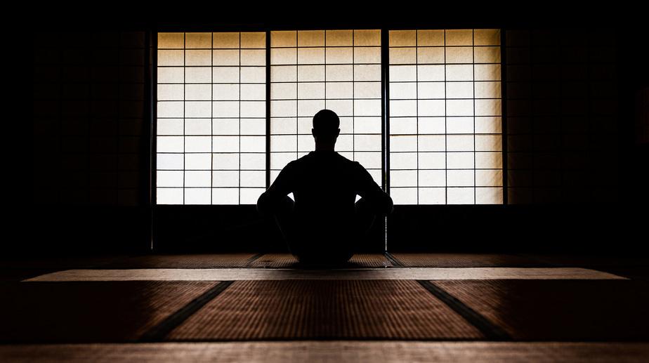 person meditating in zen room