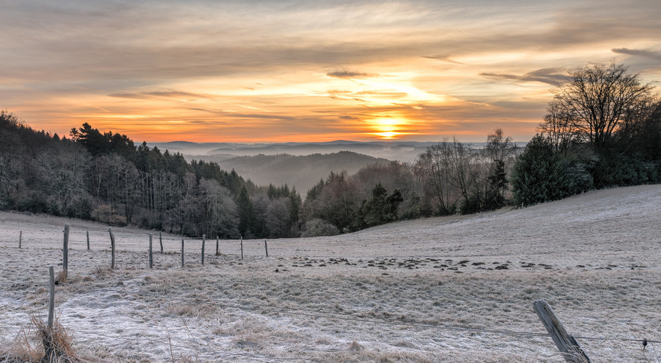 scenic morning frost over hills with sunrise
