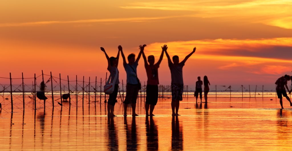 people celebrating no excuses on beach at sunset