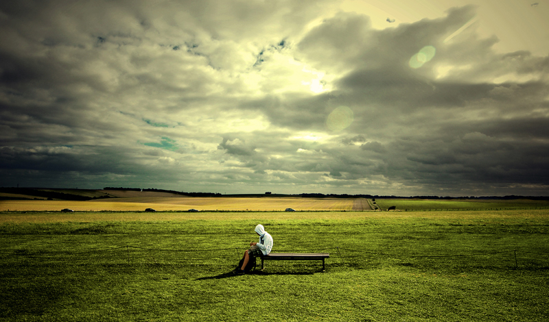 person sitting loner in a field