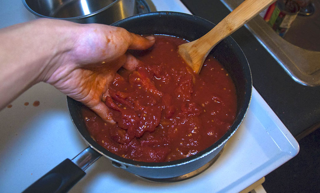 person with hand in marinara sauce