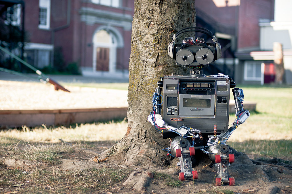 robot sitting in front of a tree
