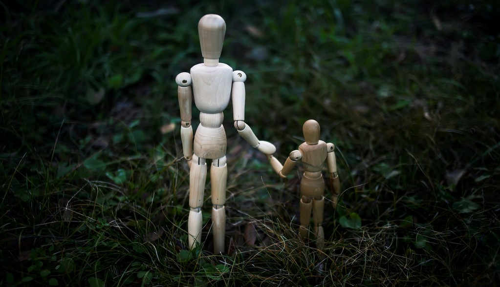 two wooden figurines holding hands