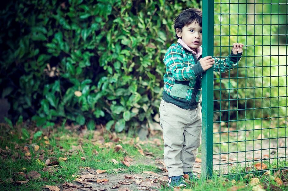 kid hiding behind a gate