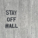 "a cement wall w/ ""stay off wall"" spray painted on it"