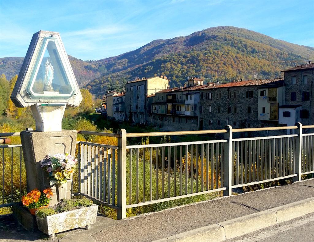 a saint statue on a bridge near a quaint town in italy, like faith or hope