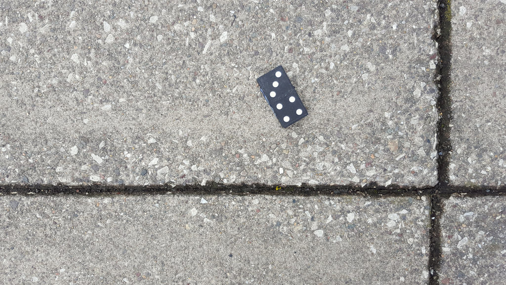 a single domino lying on pavement