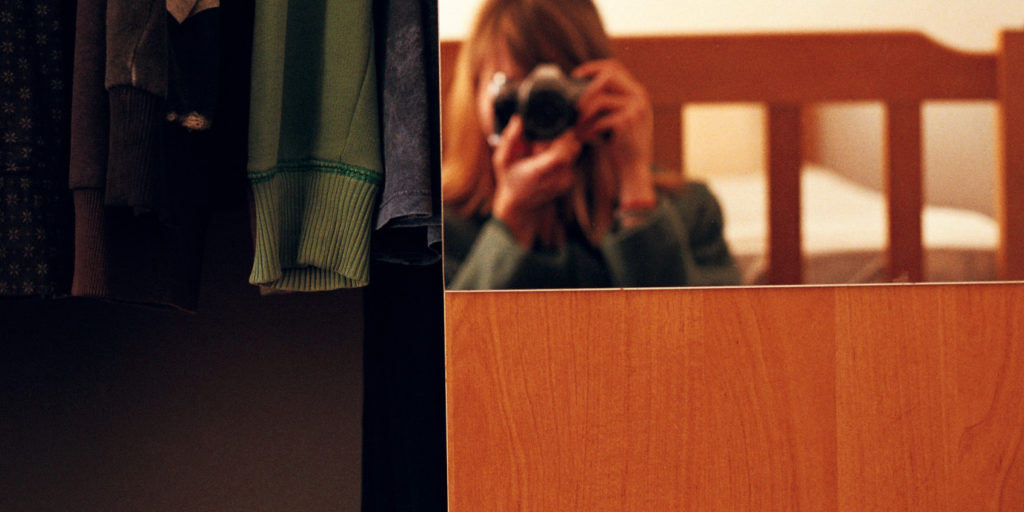 woman taking a photo of herself in the mirror