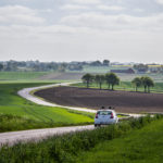 white car driving down an open road