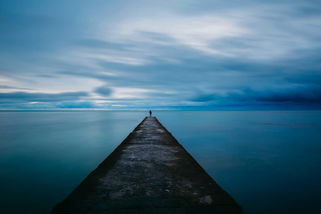 an image of a person standing alone on a lake dock